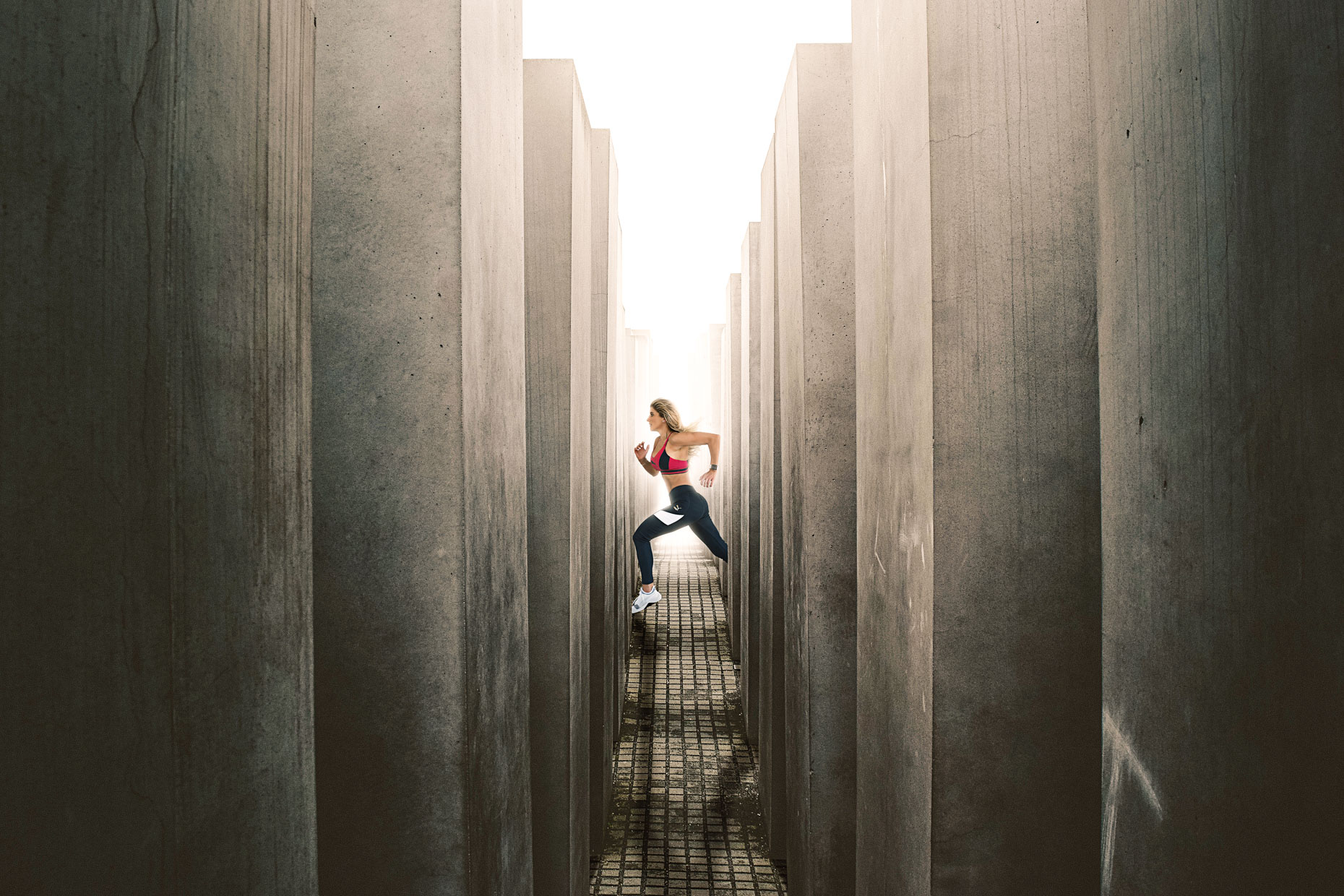 Runner sprinting between concrete pillars - conceptual composite photography